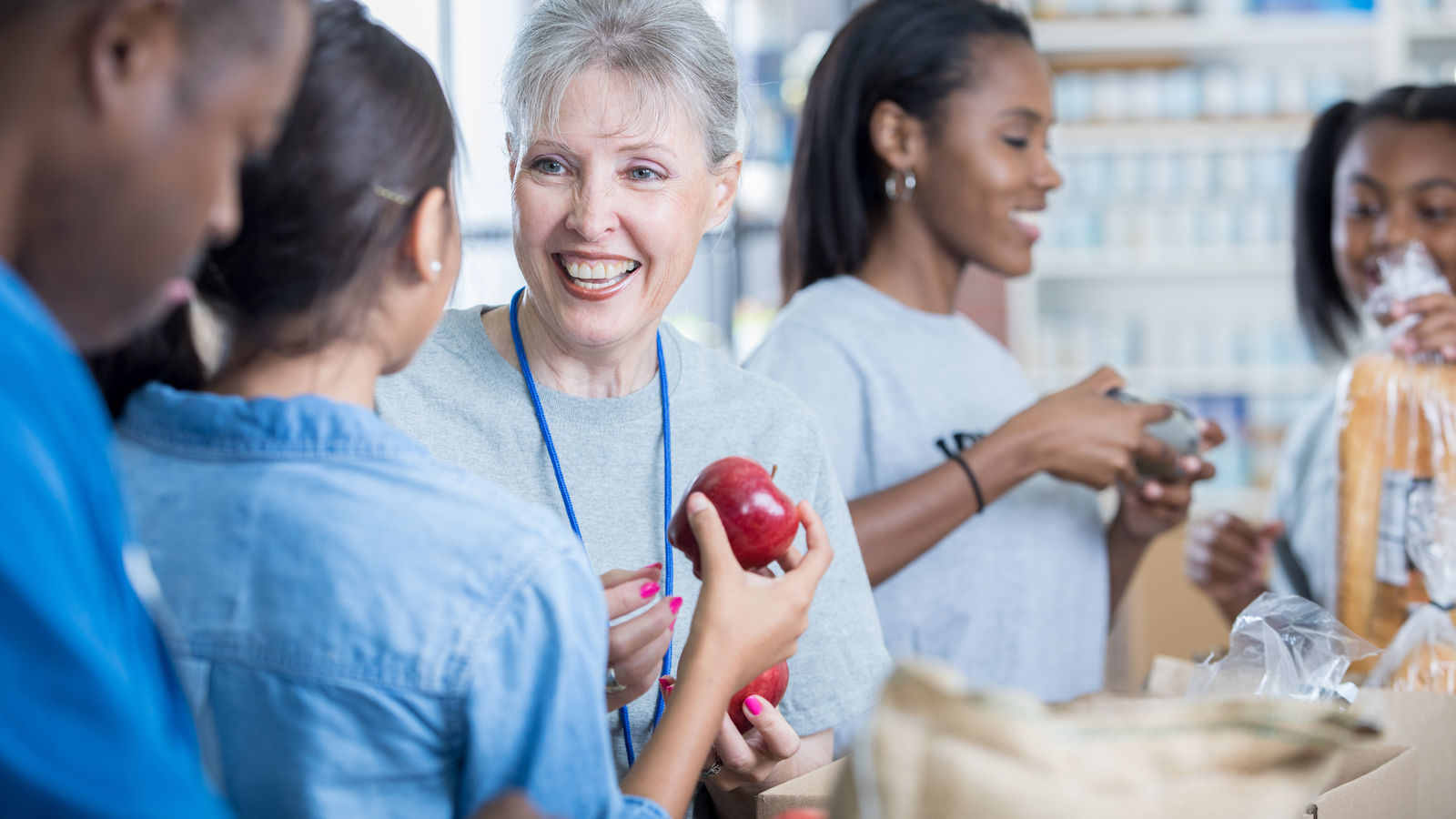 People Hold Apples at Foodbank