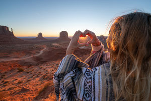 Young woman in the American desert making heart shape frame with hands loving road trip adventure stock photo Arizona, Monument Valley, USA, Utah, Desert