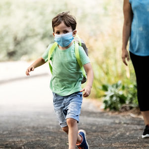 Healthy child with COVID mask running and getting exercise.