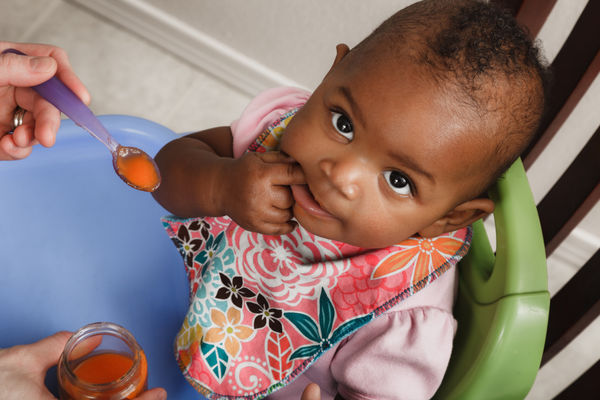 Baby being spoon fed vegetables
