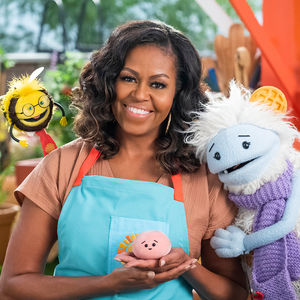 Waffles and Mochi characters posing with former First Lady Michelle Obama