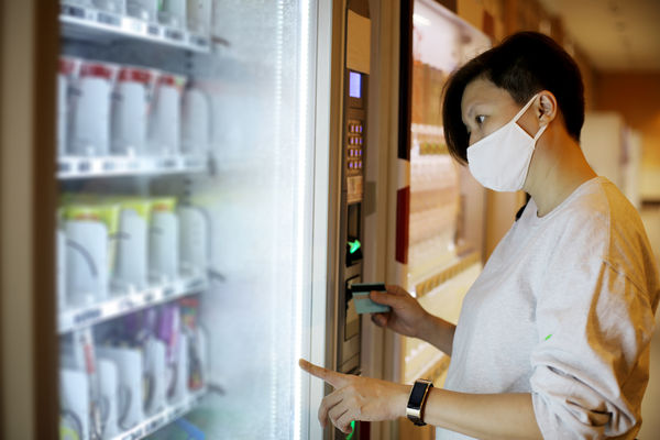 Women in mask looking at vending machine