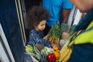 Child looking at a box of produce