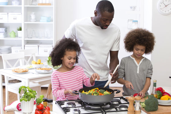 Photo of a father and two children cooking a meal together.