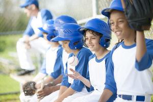 Kids baseball team sitting on a bench.