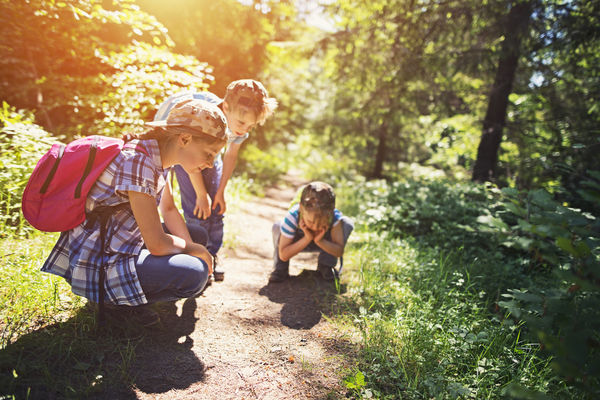 Young hikers stop to observe an object on the ground during a hike.