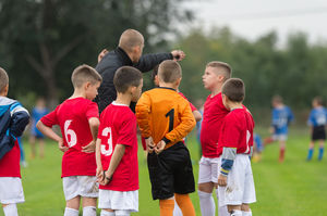 Youth soccer coach gives pep talk to team.