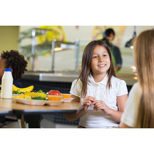 Elementary school student in cafeteria holding a lunch tray with healthier food options.
