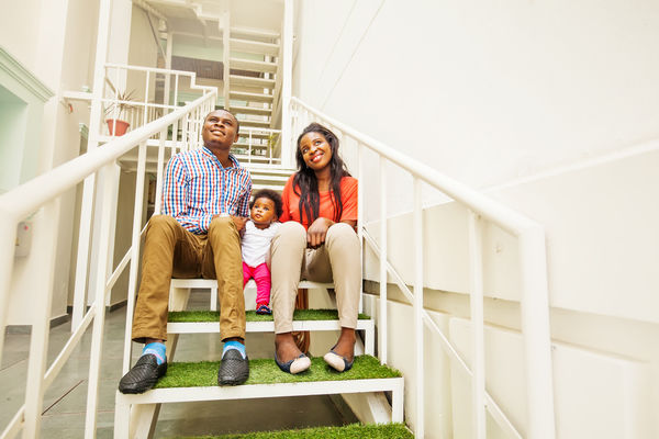 Family sitting on stairs in apartment complex.