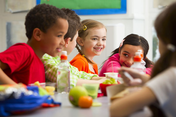 Photo of diverse group of children eating a healthy lunch at school.
