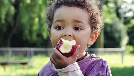 Image of young child eating an apple in Partnership for a Healthier America's 2016 Annual Progress Report.