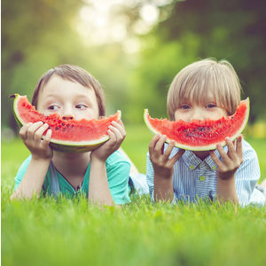Image of two children eating watermelon slices outdoors.
