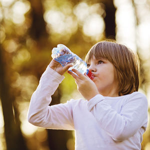 Image of young girl drinking water outdoors.