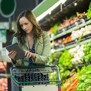 Image of a person using a health app to navigate through choices at the grocery store.