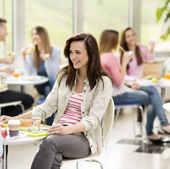 Image of college students chatting at a table in a campus dining facility.