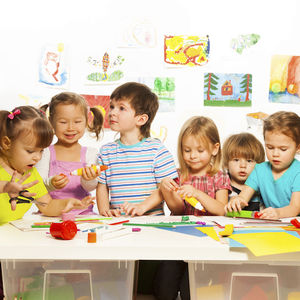 Image of preschool children at a table doing arts and crafts.