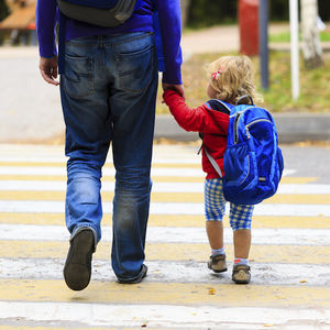 Image of child holding a parent's hand while walking to the first day of kindergarten.