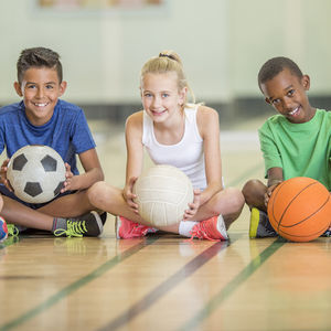 Image of a diverse group of children sitting on a gym floor and holding sports balls.