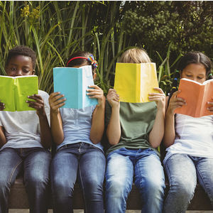 Image of a group of children sitting down and holding books in front of their faces.