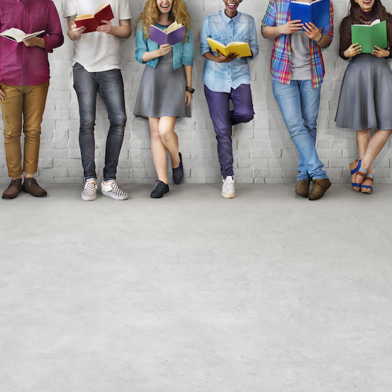 Image of college students leaning against a wall holding books.