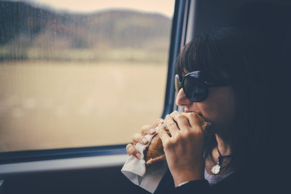 Woman eating a sandwich and staring out a train window.