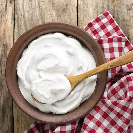 Image of plain yogurt in a bowl with a wooden spoon.