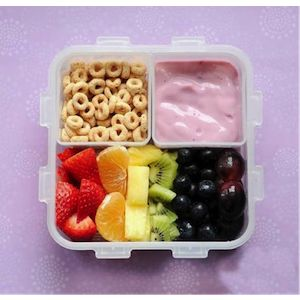 Image of whole grain cereal, yogurt and fruit in a children's lunchbox container.