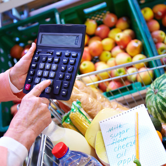 Image of a person holding a calculator in front of produce at the grocery store.