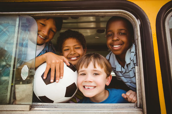 Image of elementary school boys with their heads poking out the window of a yellow school bus.
