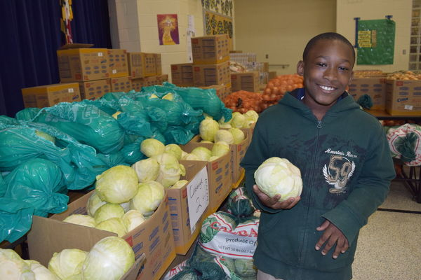 Kid with cabbage at Capital Area Food Bank in Washington DC