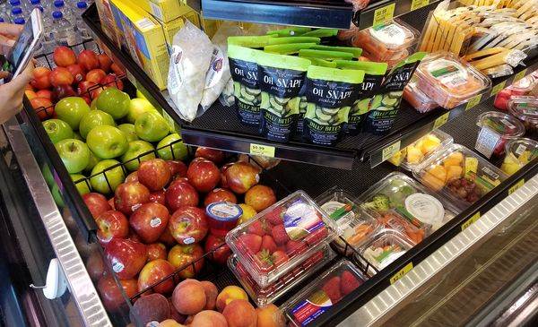 Images of fresh and healthier food options such as fruits and veggies available for purchase at a Kwik Trip convenience store.