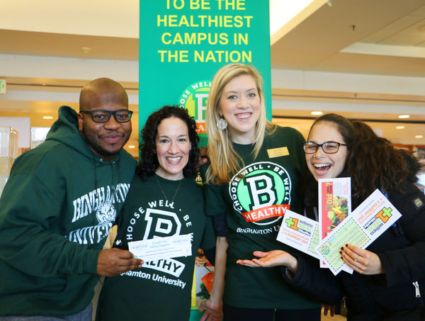 Photo of Binghamton University students holding pamphlets at a campus health fair. The school is a PHA partner participating in the Healthier Campus Initiative.