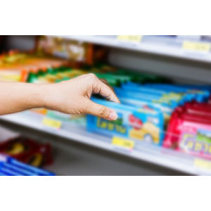 Image of a hand reaching for products on a convenience store shelf.