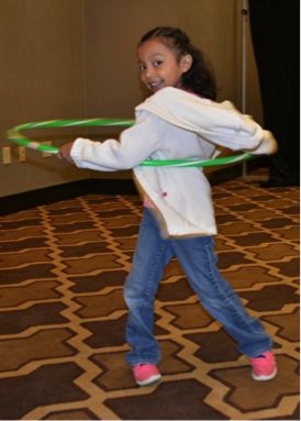 Image of a child hula hooping during on-site childcare provided by Bright Horizons Family Solutions at Partnership for a Healthier America's Building a Healthier Future Summit.
