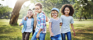 Image of a group of diverse children walking in a field.
