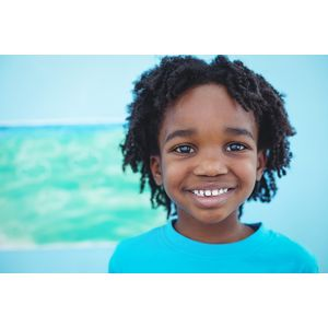 A child standing in front of a blue background.