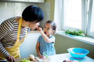 Daughter feeding her mother a carrot