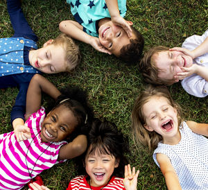 Group of diverse children laying in the grass looking up into the photographer's camera.