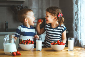 Image of two kids eating strawberries and milk.
