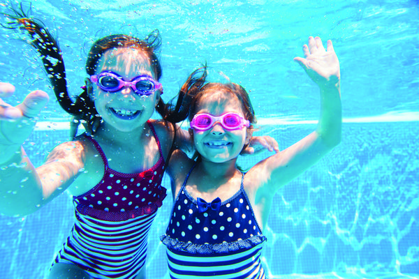 Image of two young girls swimming and posing in a pool.