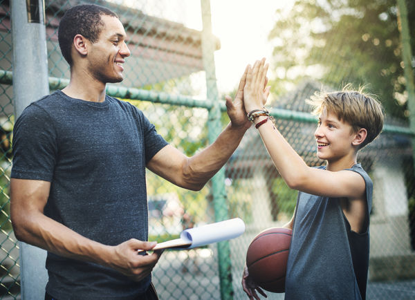 Image of a man and young boy giving one another a high five after playing basketball.
