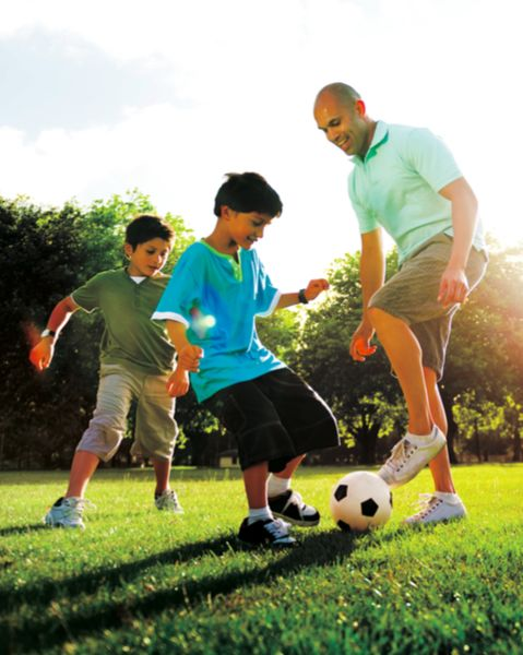 Image of a man and two young boys playing soccer in a field.