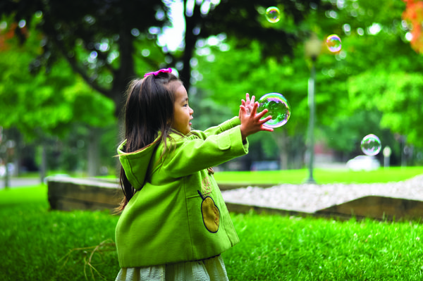 Image of a girl in a rain coat popping bubbles outdoors.