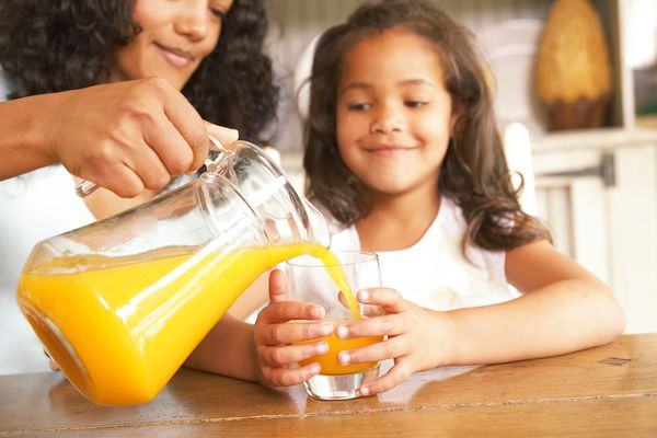 Image of a mom and daughter drinking glasses of orange juice.