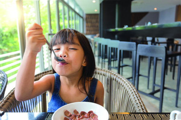 Image of a small child eating in a restaurant.