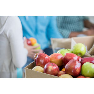 Image of a box of donated apples in a food bank.