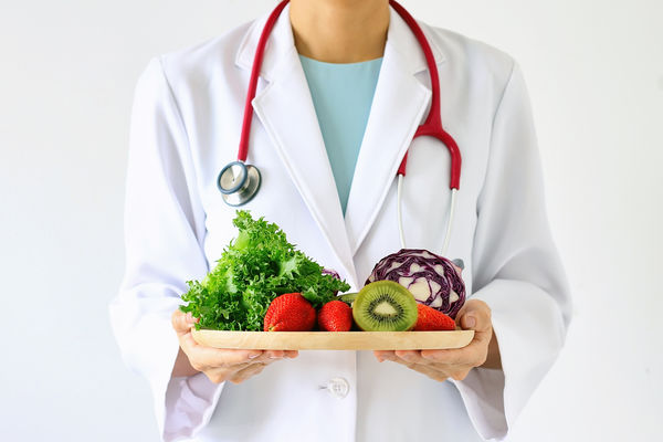 Image of a doctor in a lab coat holding a tray of fruits and vegetables.