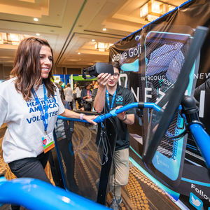 A volunteer at Partnership for a Healthier America's 2018 Innovating a Healthier Future Summit tests Blue Goji's virtual reality treadmill on the event Expo floor.